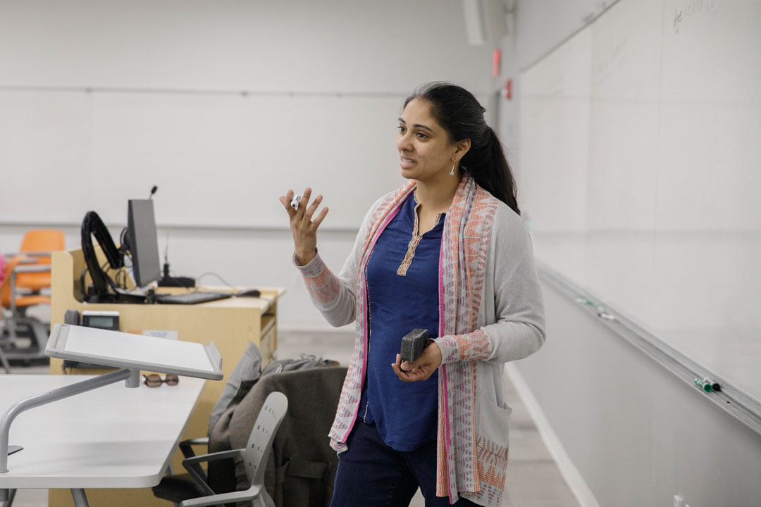 Professor Sangeeta Prasad teaches at the front of a classroom next to a whiteboard